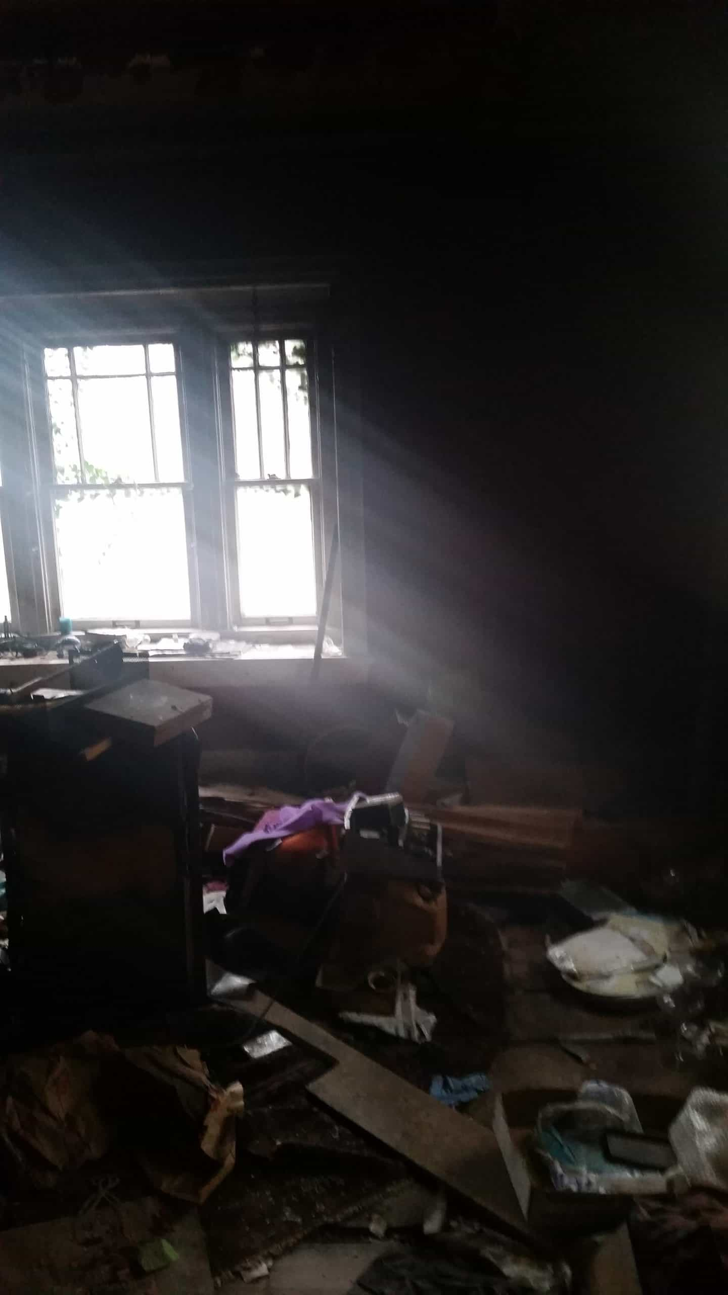 Interior of a dark house with debris piled on the floor and a window letting light in.
