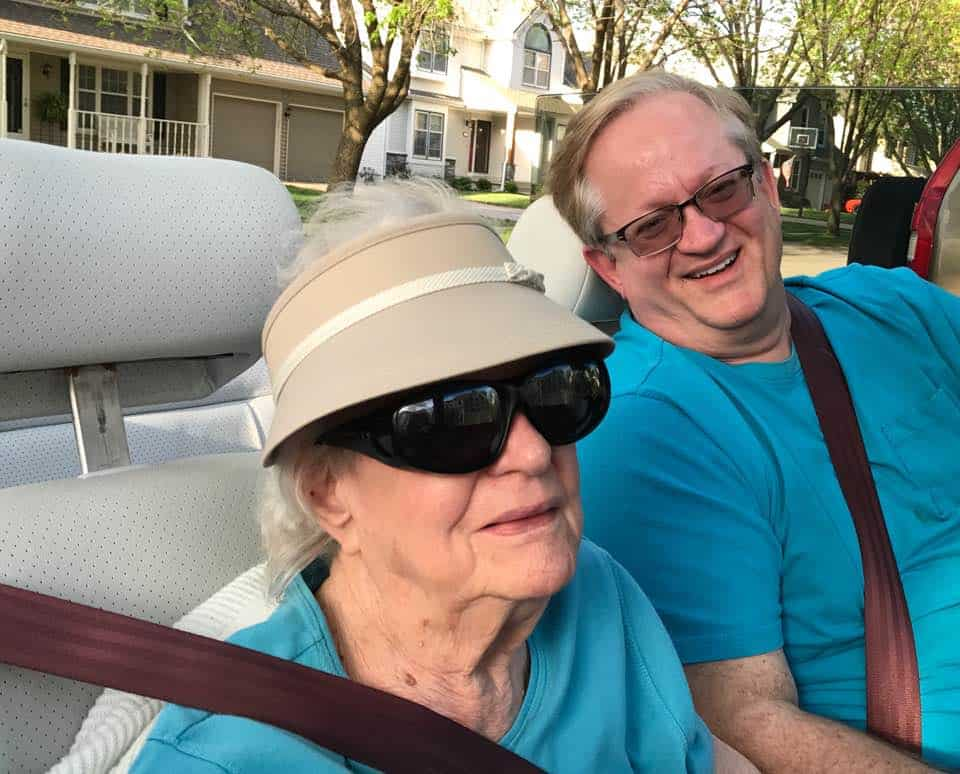 a man and woman sitting in a car and smiling